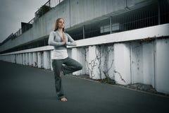Jong meisje die op één voet mediteren Stock Afbeeldingen