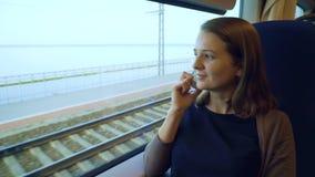 Jong meisje die op celtelefoon spreken op de trein stock footage