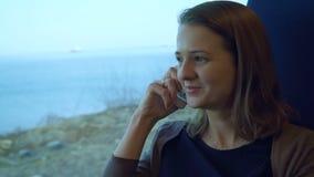 Jong meisje die op celtelefoon spreken op de trein stock videobeelden