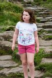Jong Meisje die op de rotsen bij de Reuzeverhoogde weg van ` lopen s Stock Foto's
