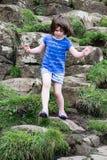 Jong Meisje die op de rotsen bij de Reuzeverhoogde weg van ` lopen s Royalty-vrije Stock Afbeeldingen