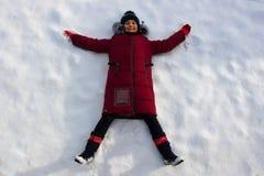 Jong meisje die op de sneeuwwitte sneeuw liggen stock foto
