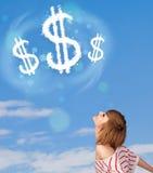 Jong meisje die op de wolken van het dollarteken op blauwe hemel richten Stock Afbeeldingen