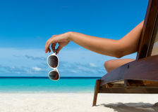 Jong meisje die op een strandlanterfanter liggen met in hand glazen stock foto