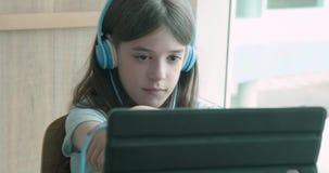 Jong meisje die op haar glimlachen van de tabletcomputer letten bij de camera stock footage