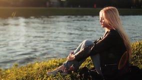 Jong meisje die op het groene gras dichtbij de rivier bij zonsondergang rusten stock videobeelden