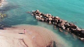 Jong meisje die op zandig strand lopen Aantrekkelijke vrouw in rode kleding op strand Satellietbeeld van mooi strand met duidelij stock footage