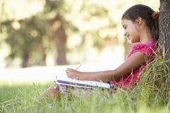 Jong Meisje die in Platteland schetsen die tegen Boom leunen stock foto