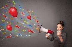 Jong meisje die pret hebben, die in megafoon met ballons schreeuwen Royalty-vrije Stock Foto's