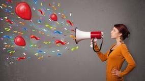 Jong meisje die pret hebben, die in megafoon met ballons schreeuwen Stock Afbeeldingen