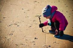 Jong meisje die pret op de winter Baltisch strand hebben Stock Afbeeldingen
