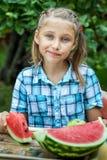 Jong meisje die rijpe watermeloen eten stock foto's