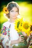 Jong meisje die Roemeens traditioneel de zonnebloemen openluchtschot dragen van de blouseholding. Portret van mooi blondemeisje me Royalty-vrije Stock Foto's