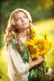Jong meisje die Roemeens traditioneel de zonnebloemen openluchtschot dragen van de blouseholding. Portret van mooi blondemeisje me Stock Foto's