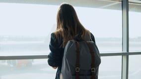 Jong meisje die smartphone gebruiken dichtbij luchthavenvenster De gelukkige Europese vrouw met rugzak gebruikt mobiele app in te Royalty-vrije Stock Fotografie