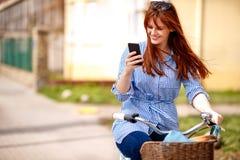 Jong meisje die smartphone met het berijden van fiets in stad gebruiken Stock Afbeeldingen