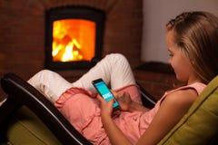 Jong meisje die smartphonezitting voor open haard gebruiken Royalty-vrije Stock Foto's