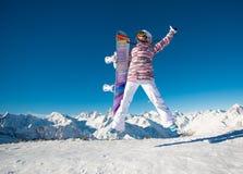 Jong meisje die snowboarder in de alpiene bergen springen Stock Fotografie