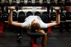 Jong meisje die sommige spieren met zware domoren bouwen stock foto