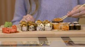 Jong Meisje die Sushi met Eetstokjes eten stock videobeelden