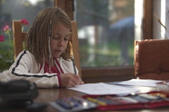 Jong meisje die thuiswerk met potlood en document doen Royalty-vrije Stock Foto