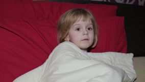 Jong meisje die TV-op televisie op het bed letten stock videobeelden