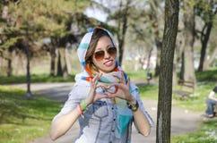 Jong meisje die van de lente genieten en een hartvorm met haar han maken Stock Afbeelding