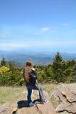 Jong meisje die van tijd op de bovenkant van de berg genieten Stock Afbeelding
