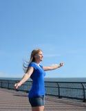 Jong meisje die van zon en wind genieten door de oceaan Stock Afbeeldingen