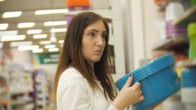 Jong meisje die voor meubilair, glazen, schotels en huisdecor winkelen in opslag stock videobeelden