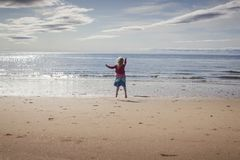 Jong meisje die voor vreugde op een strand springen stock fotografie