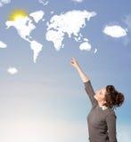 Jong meisje die wereldwolken en zon bekijken op blauwe hemel Royalty-vrije Stock Fotografie