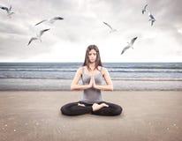 Jong meisje die yoga op het strand doen royalty-vrije stock fotografie