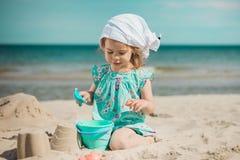 Jong meisje die zandkasteel op strand maken Stock Afbeelding
