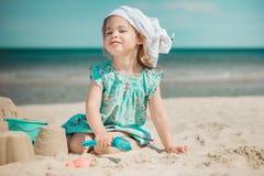 Jong meisje die zandkasteel op strand maken Stock Afbeeldingen