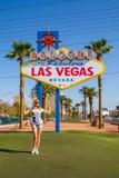 Jong meisje die zich door het teken van Las Vegas in Nevada bevinden royalty-vrije stock afbeeldingen