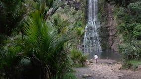 Jong meisje die zich voor een reusachtige waterval in een bos bevinden stock video