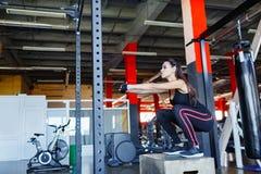 Jong meisje die zitten-UPS op een platform in de gymnastiek doen stock foto's