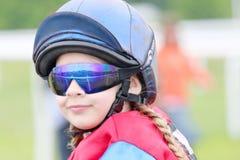 Jong meisje die zonglazen dragen die op een poney zitten Royalty-vrije Stock Afbeelding
