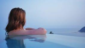 Jong meisje die in zwembad de afstand onderzoeken stock footage