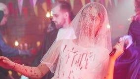 Jong meisje in een bloedige bevlekte bruidkleding met een sluier op haar gezicht en een bloedig mes als Halloween-vermomming stock videobeelden