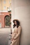 Jong meisje in een hoed en laag op achtergrond van theaterkolommen Stock Foto