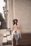 Jong meisje in een hoed en laag op achtergrond van theaterkolommen Stock Fotografie