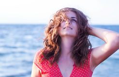 Jong meisje in een rode kleding die op de achtergrond van het overzees glimlachen stock afbeeldingen