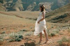 Jong meisje in een witte kleding in hippiestijl die in bergen stellen royalty-vrije stock fotografie