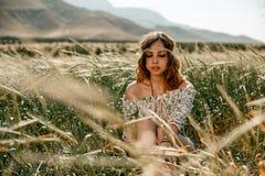 Jong meisje in een witte kleding in hippiestijl het stellen op een tarwegebied royalty-vrije stock afbeelding