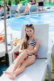 Jong meisje in een zwempak op een plank door de pool Stock Afbeelding
