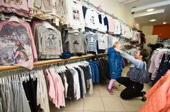 Jong meisje en haar moeder die voor nieuwe kleren winkelen Royalty-vrije Stock Foto's