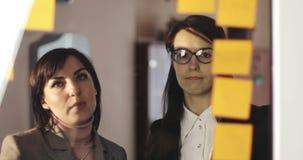Jong meisje en Midden oude bedrijfsvrouw die de ontwerper van de glasmuur met post-itnota's bekijken en ideeën op hen verbinden stock videobeelden