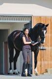 Jong meisje en zwart paard royalty-vrije stock afbeelding